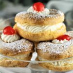 glass plate piled with zeppole with ricotta filling and cherry on top