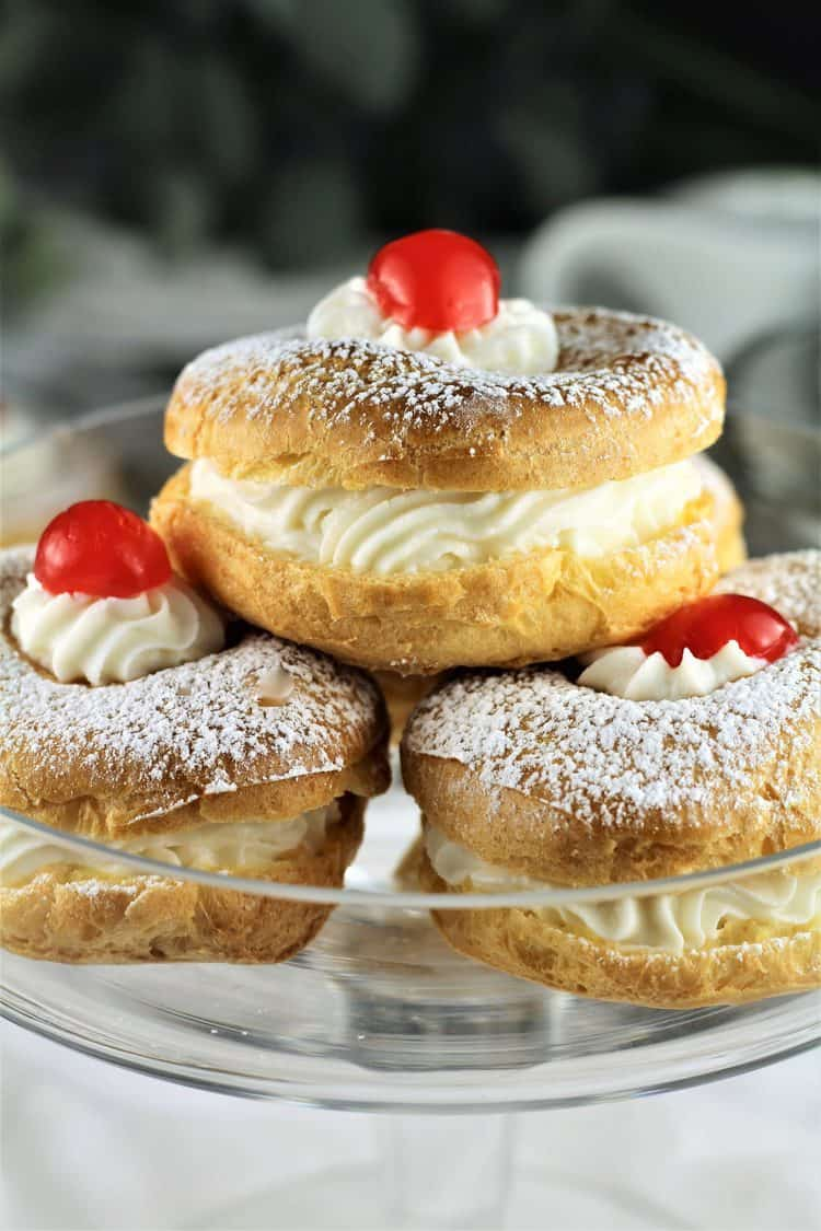 closeup of 3 zeppole with cherry on top on glass plate