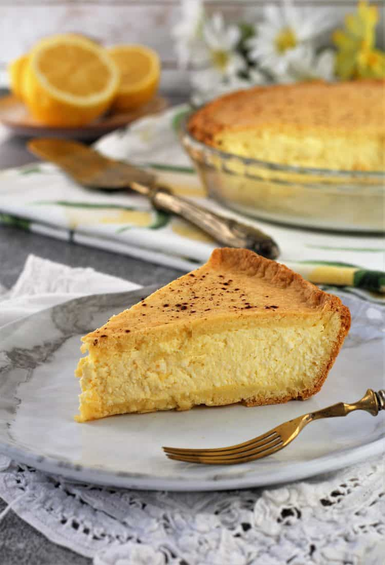wedge of ricotta pie on white plate with fork