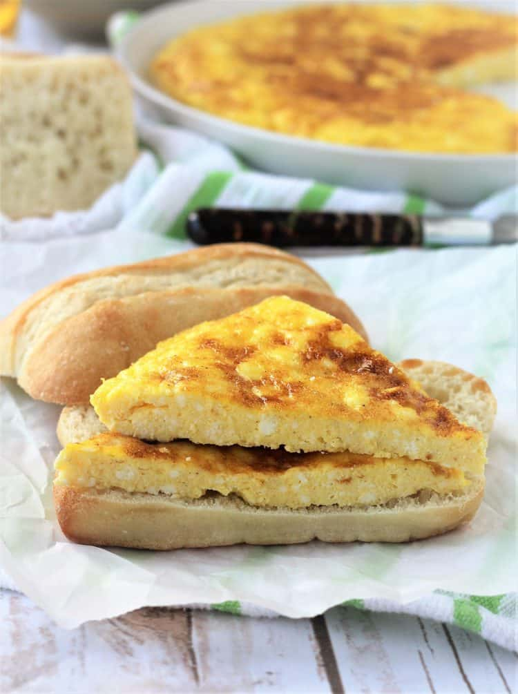 frittata with ricotta in a panini on wax paper and frittata with bread behind it