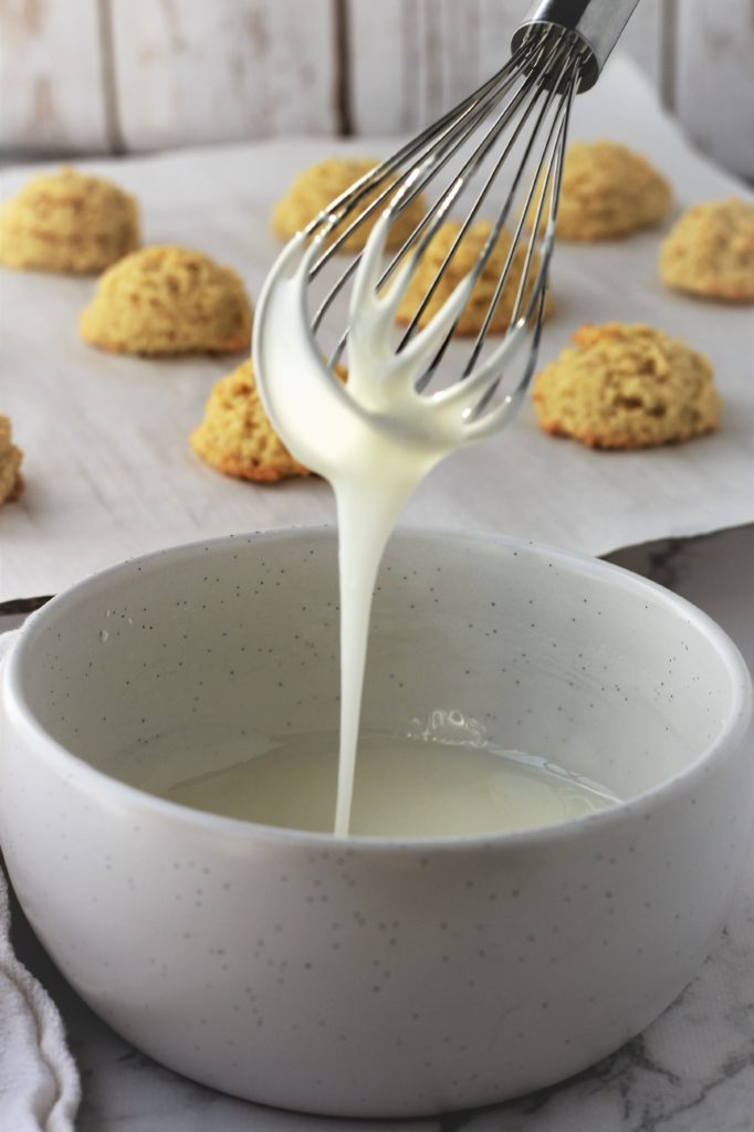 whisked icing in bowl with rack of cookies in background