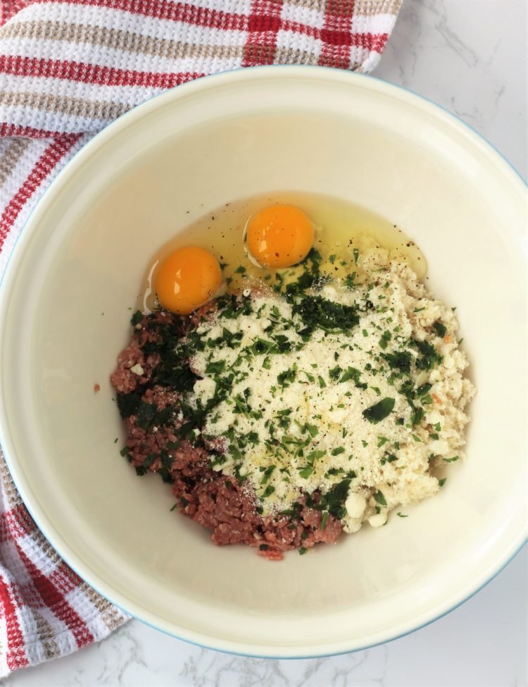 bowl with groud meat, breadcrumbs, eggs and cheese for meatballs