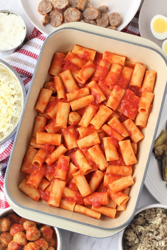 rigatoni with tomato sauce in baking dish surrounded by bowls with ingredients for pasta al forno