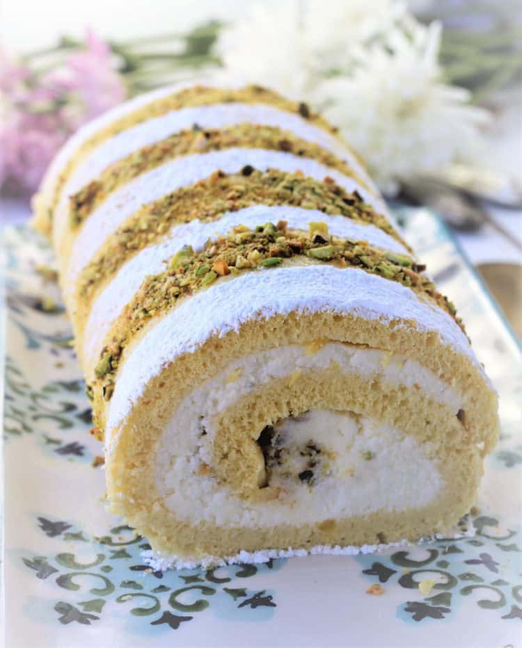 ricotta roll cake on platter topped with powdered sugar and chopped pistachios