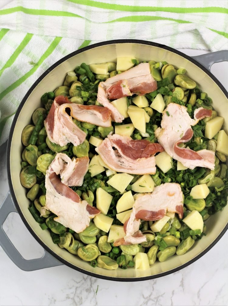 large skillet filled with peas, fava beans, potato and bacon slices