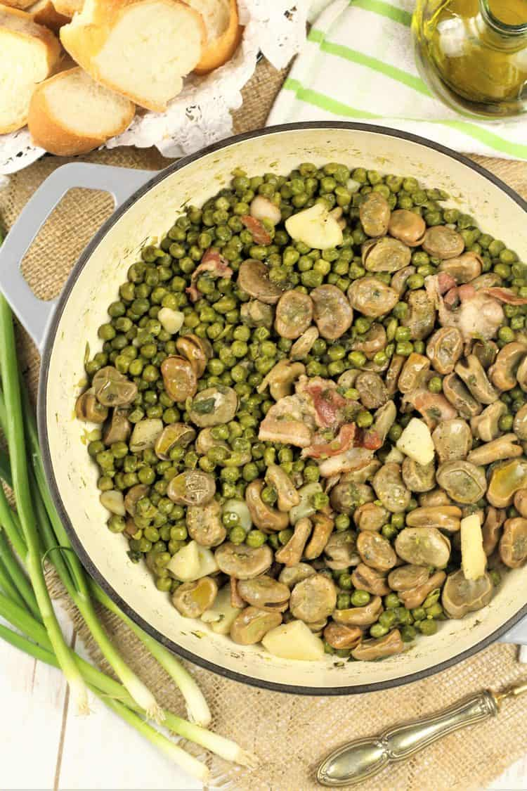 large skillet with fava beans and pea stew surrounded by bread, olive oil and green onions