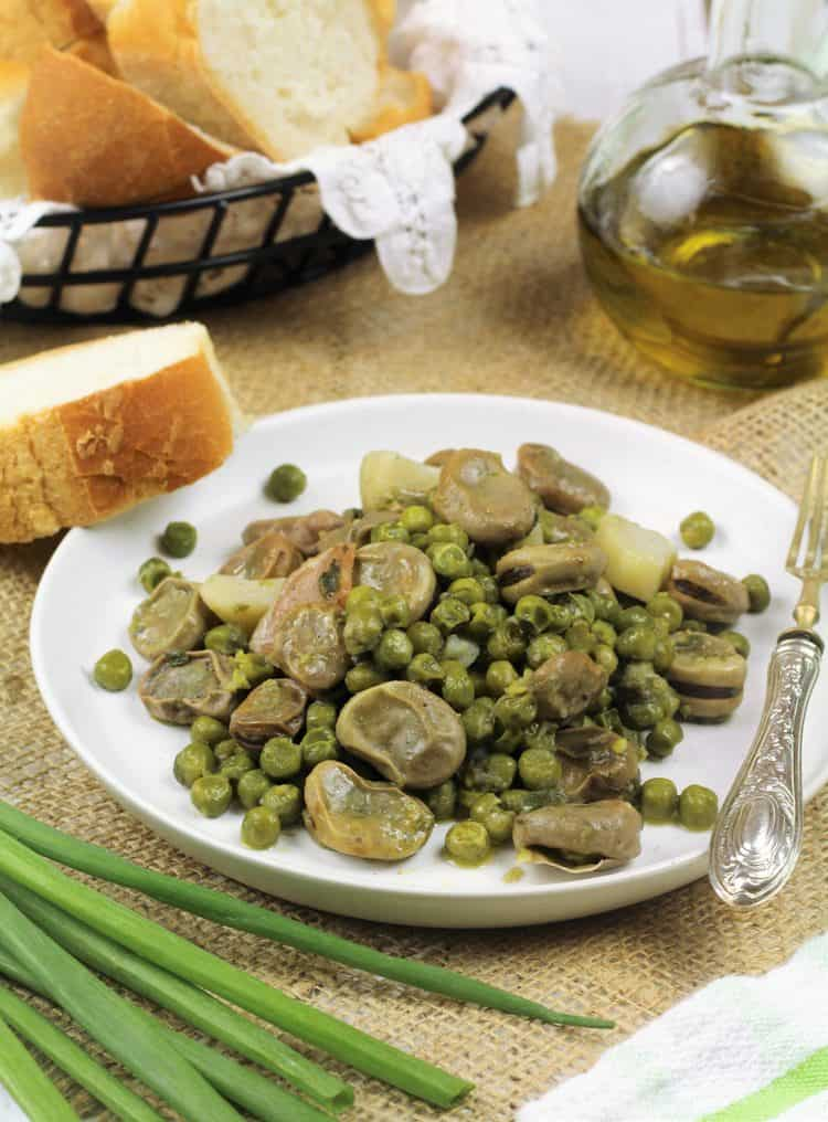 white plate filled with fava beans and peas with wedge of bread, green onions and olive oil bottle around it