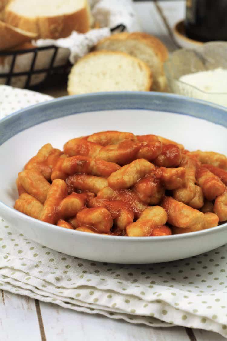 bowl of gnocchi with tomato sauce on polka doted napkin
