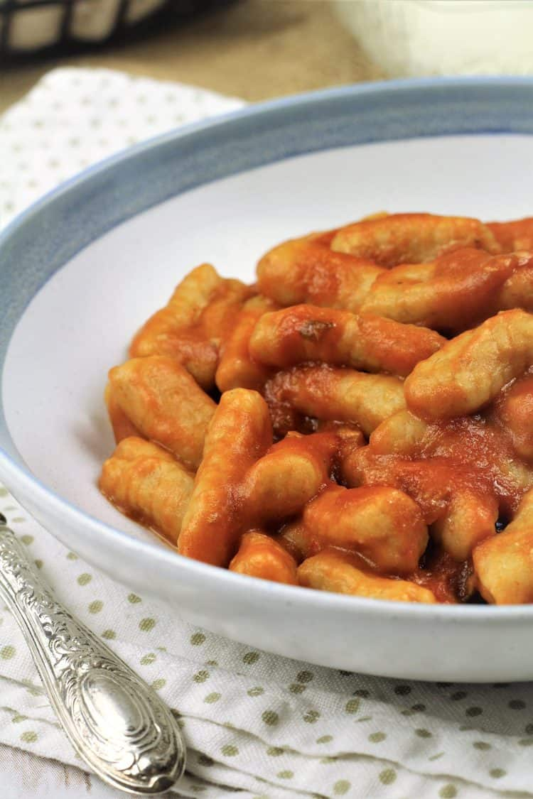 bowl of gnocchi with tomato sauce on poka doted napkin