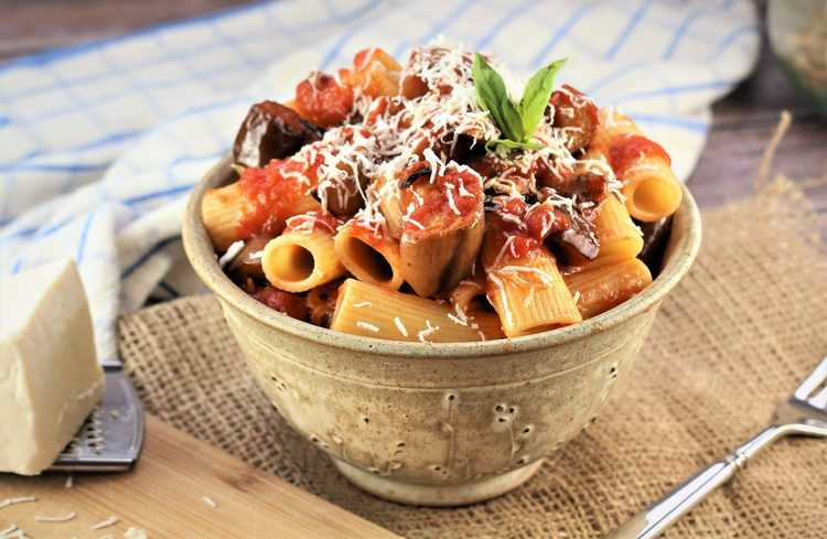 ceramic bowl filled with pasta, tomato sauce, eggplant and cheese