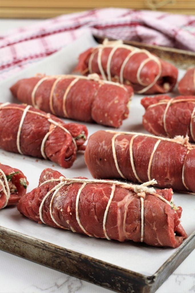 beef braciole tied in butcher's twine on baking sheet