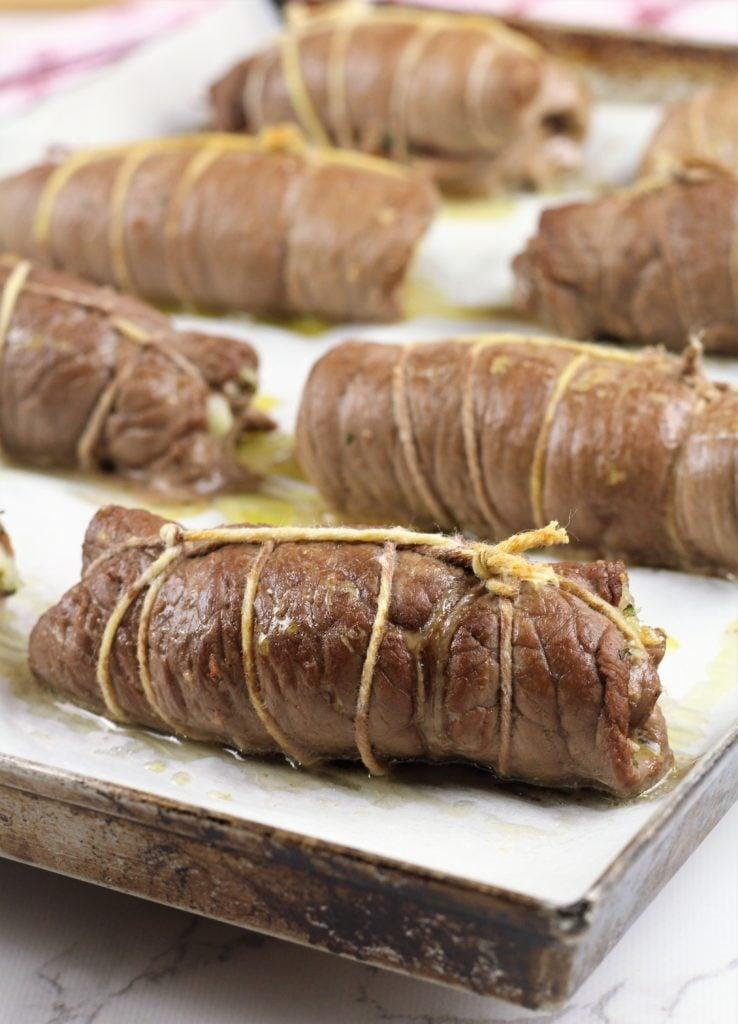 browned beef braciole on baking sheet
