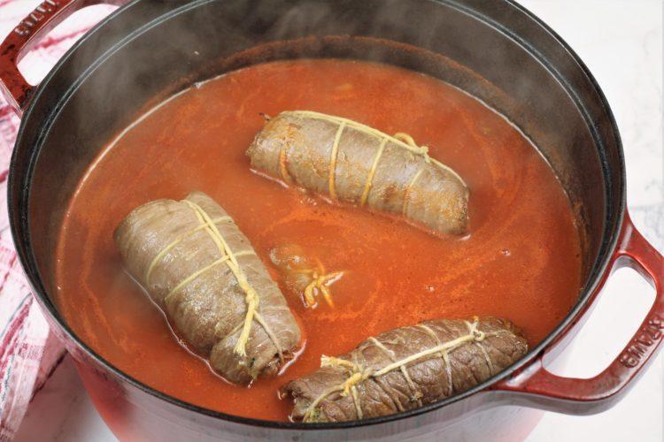 beef braciole simmering in tomtato sauce