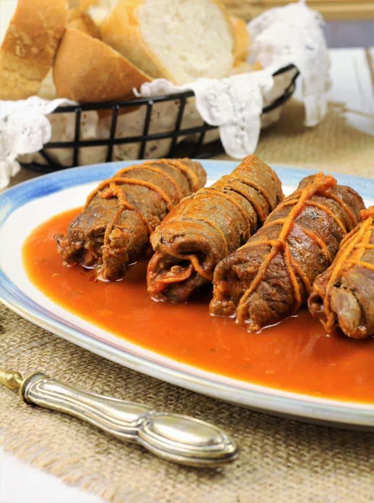 beef braciole tied in butcher's twine in tomato sauce on platter
