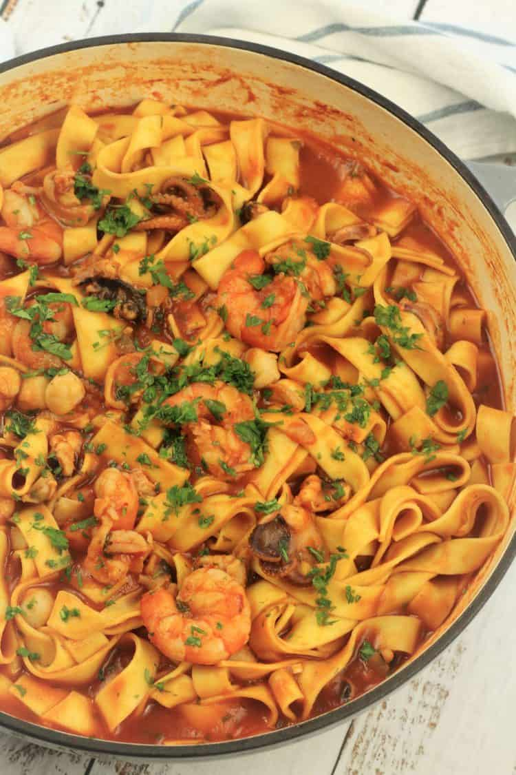 large grey skillet filled with pasta in tomato seafood sauce