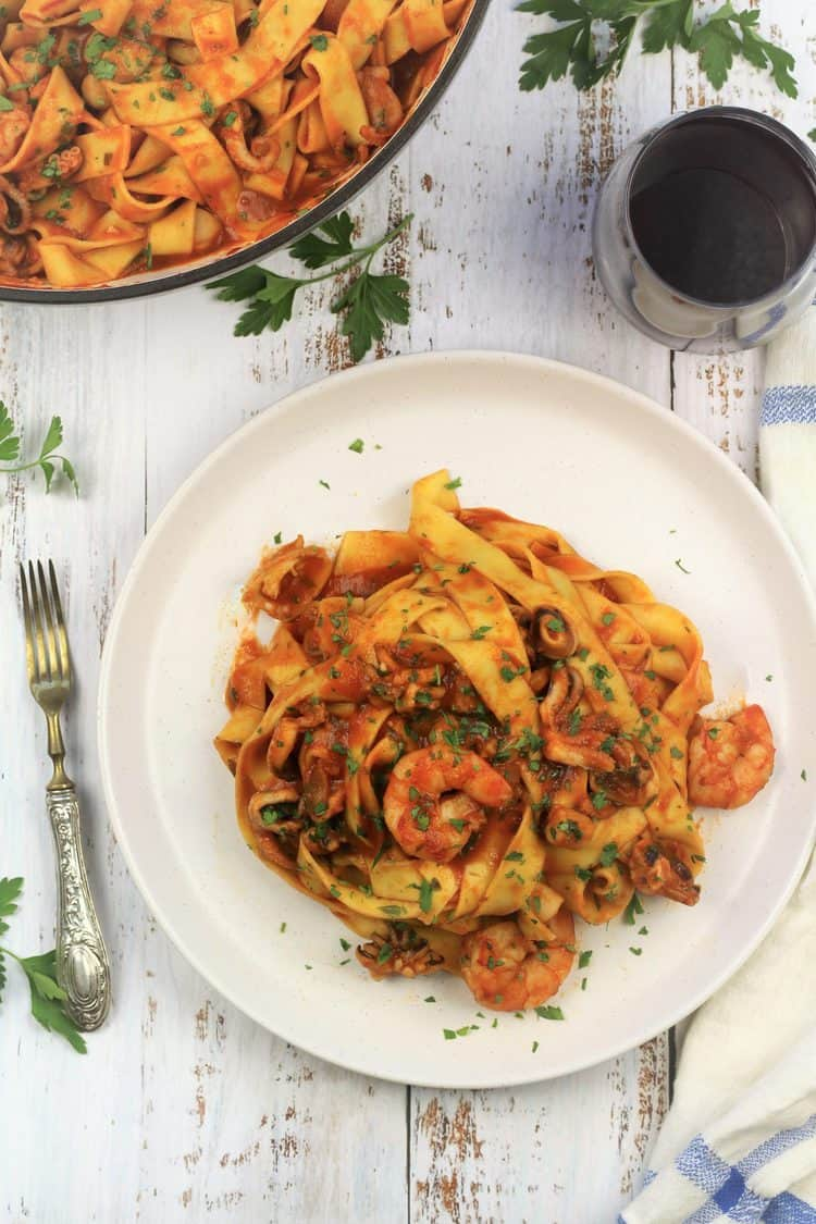 white plate with pasta in seafood tomato sauce with glass of red wine, fork and pan with pasta
