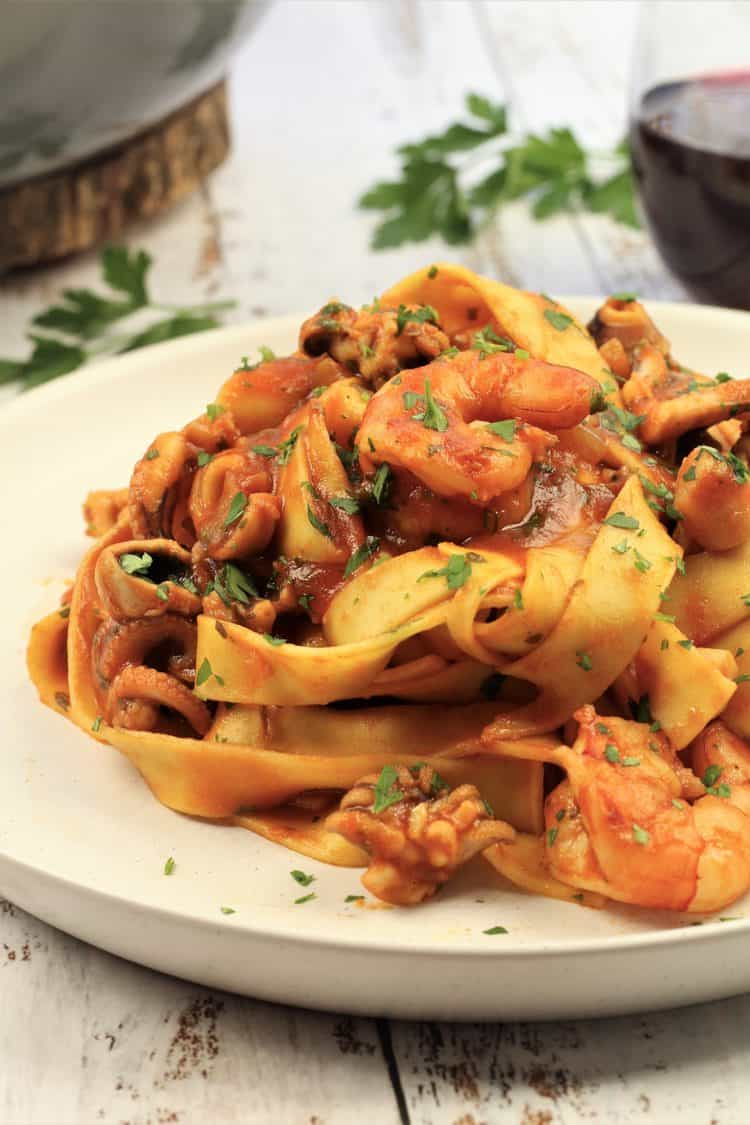 white plate piled with tagliatelle in a seafood tomato sauce