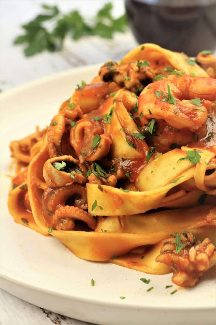 tagliatelle with seafood tomato sauce piled onto white plate
