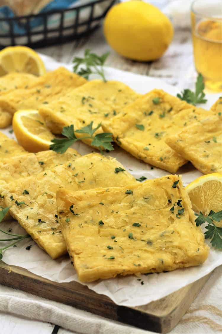 fried panelle squares on wood board with parsley sprigs and lemon wedges