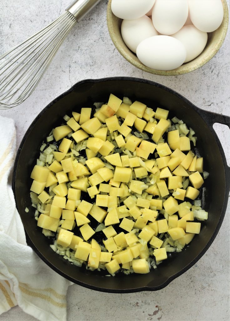 cast iron skillet with cubed potatoes and bowl of eggs with whisk behind it