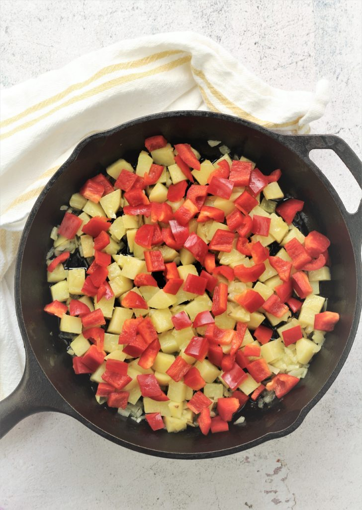 cast iron skillet with diced potatoes and red peppers