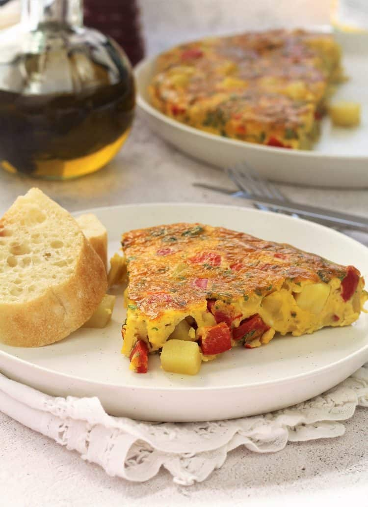 wedge of potato and red pepper frittata on white plate with bread slices