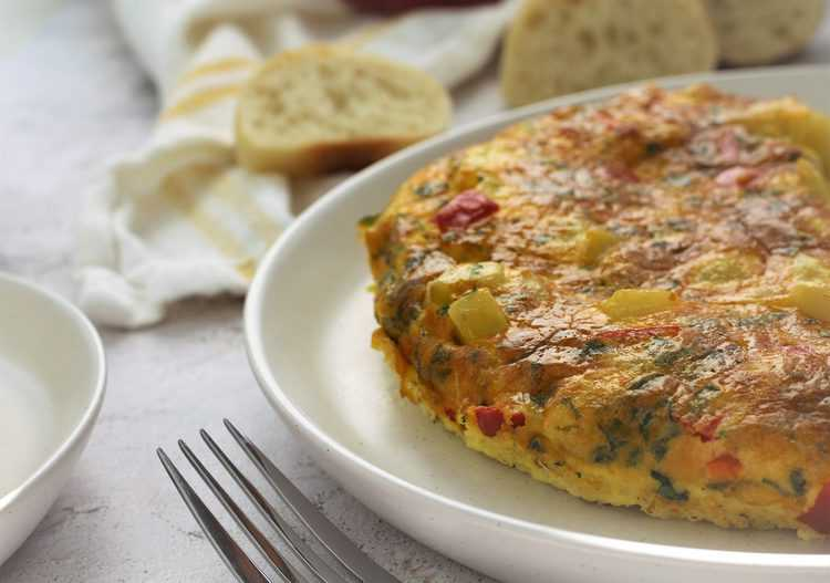 potato and red pepper frittata on round white plate with bread slices