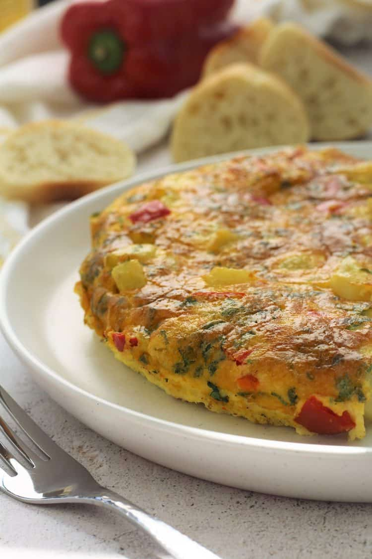 Potato and Red Pepper Frittata on white plate with fork and bread slices behind it