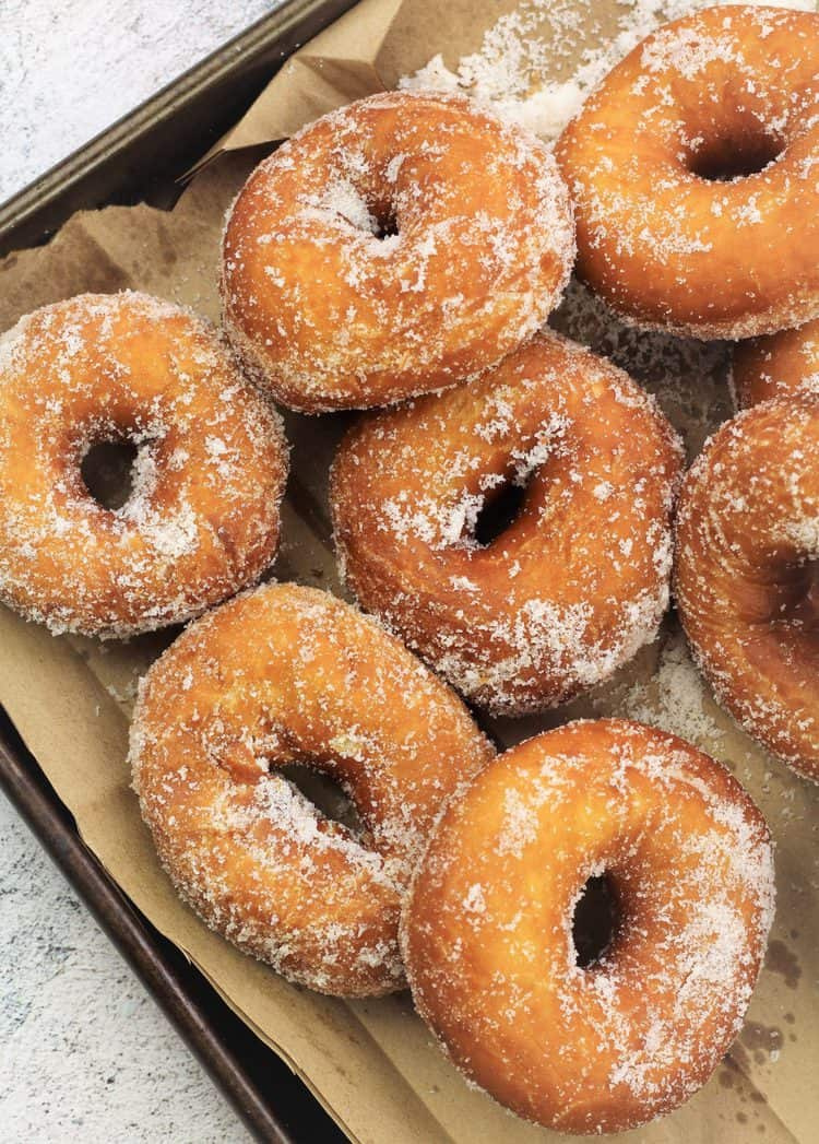 sugar coated doughnuts on brown bag covered baking sheet