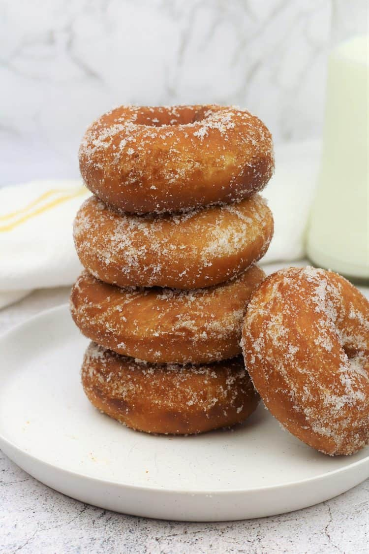 piled sugar coated doughnuts on round plate with one lying on the side