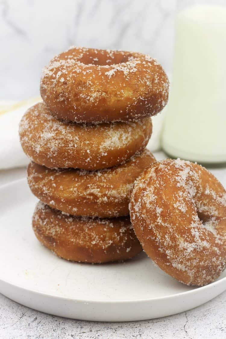 piled sugar doughnuts on round plate with one resting on the side