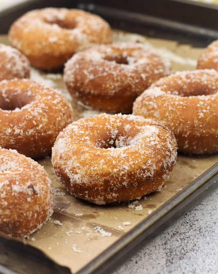 sugar coated doughnuts on brown paper bag on baking sheet
