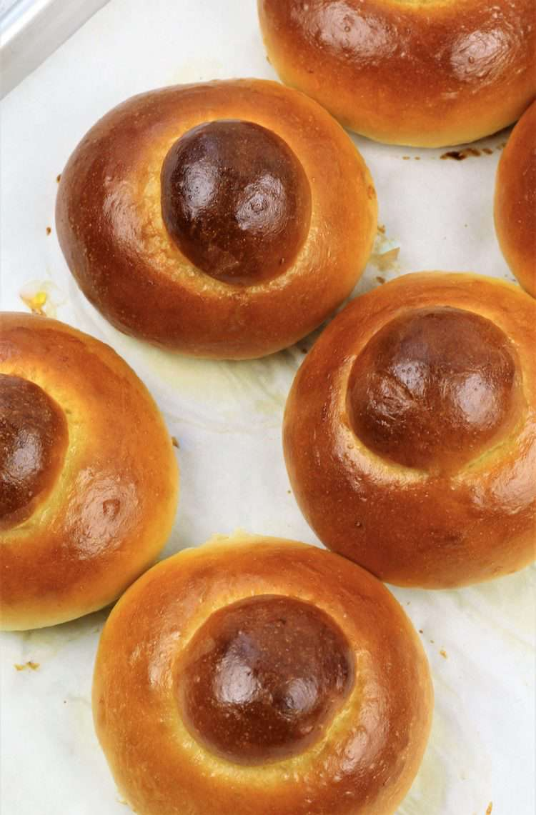 baked brioche on parchment covered baking sheet