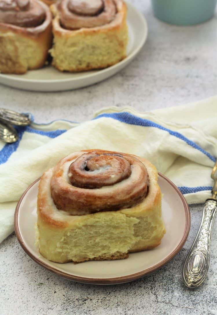 cinnamon roll on plate with plate of buns behind it