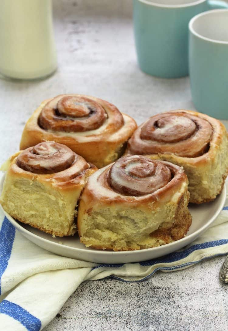 cinnamon rolls on round white plate with blue coffee mugs and bottle of milk