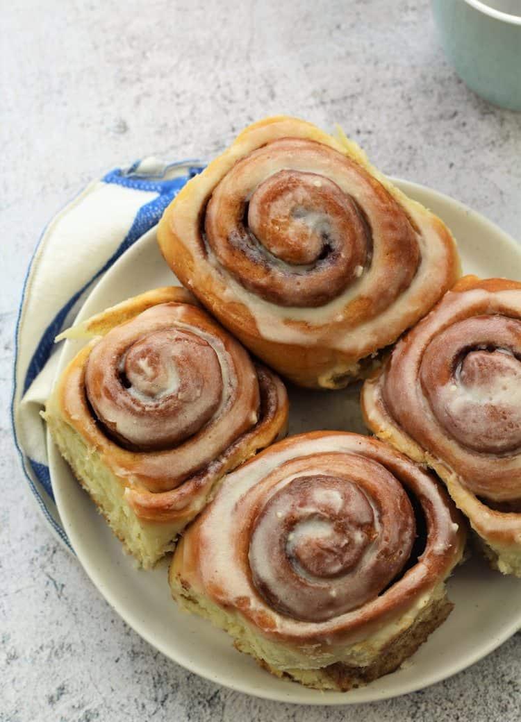 four cinnamon buns on round white plate