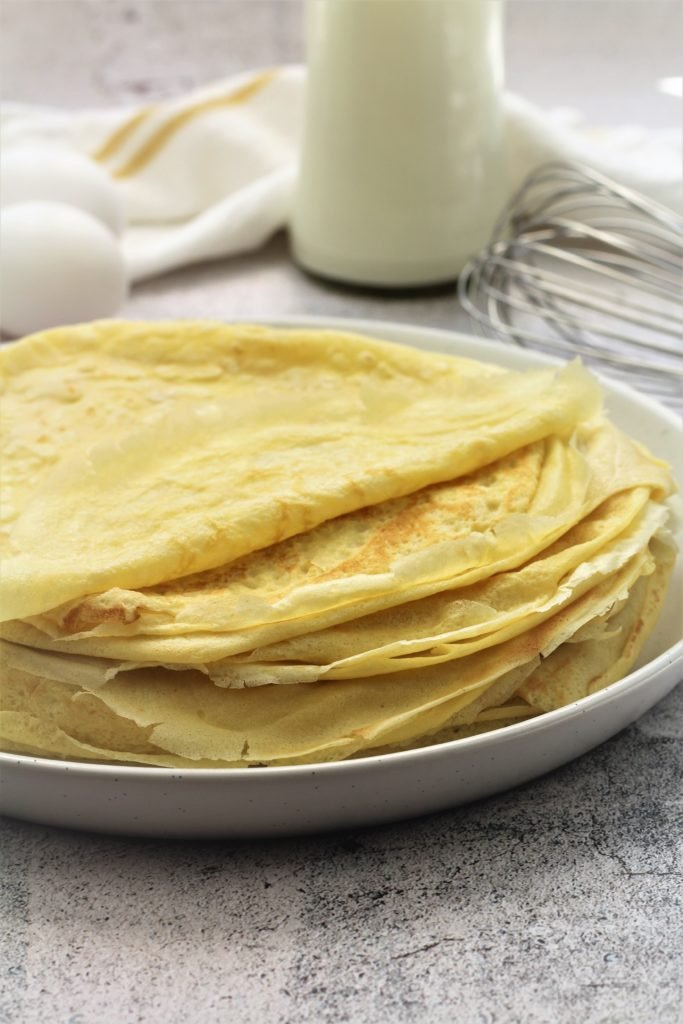 stack of crepes on round plate with eggs, milk bottle and whisk in background