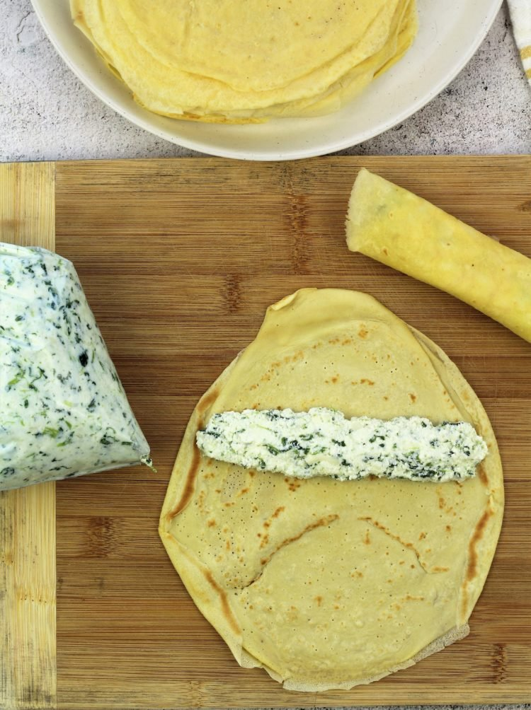 piping ricotta spinach filling into a crepe and rolling it