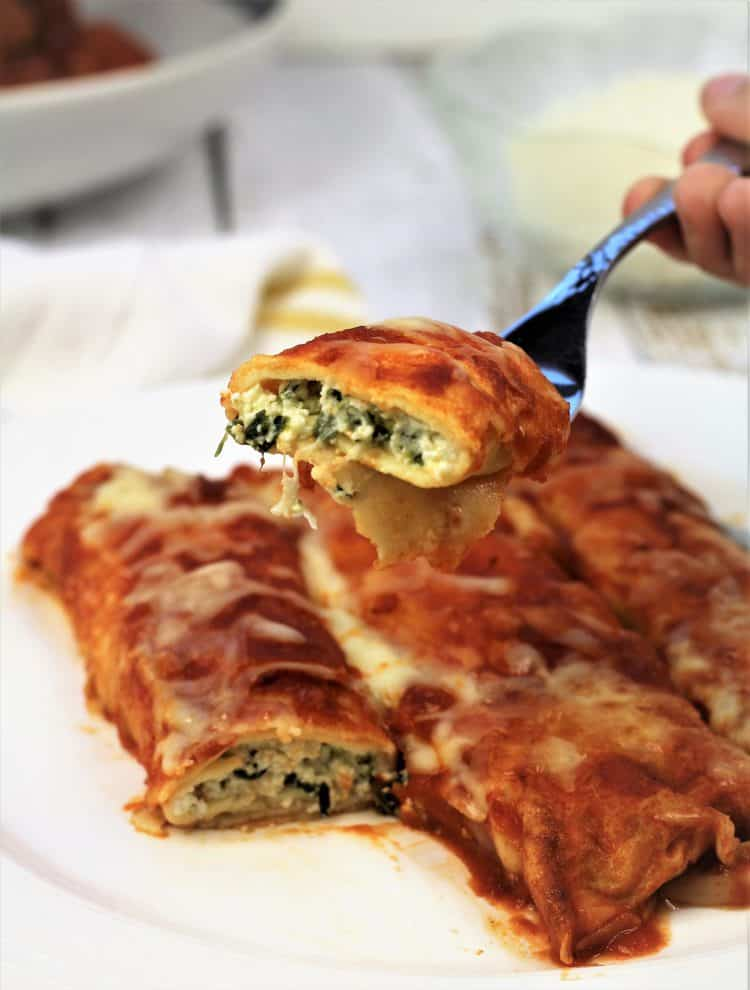 forkful of crepe cannelloni with ricotta and spinach over plate filled with cannelloni