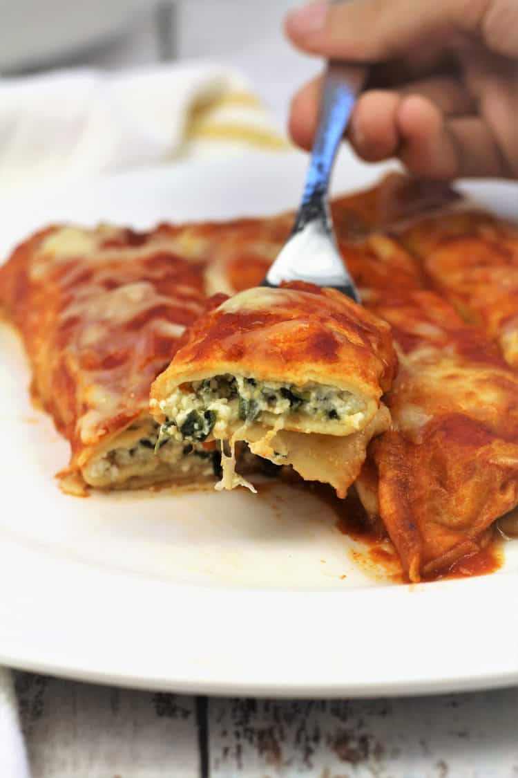 forkful of crepe cannelloni with spinach and ricotta taken from plate full of cannelloni