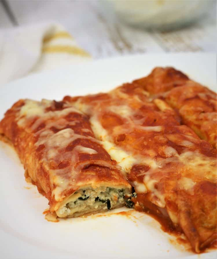crepe cannelloni with tomato sauce filled with spinach and ricotta on plate