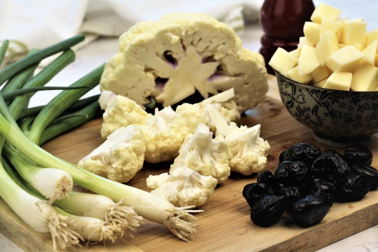 cauliflower, green onions, black olives and cubed cheese on wood board