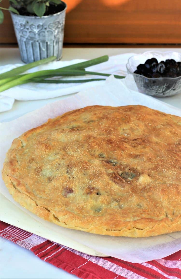 baked scacciata with cauliflower and black olives on wood board