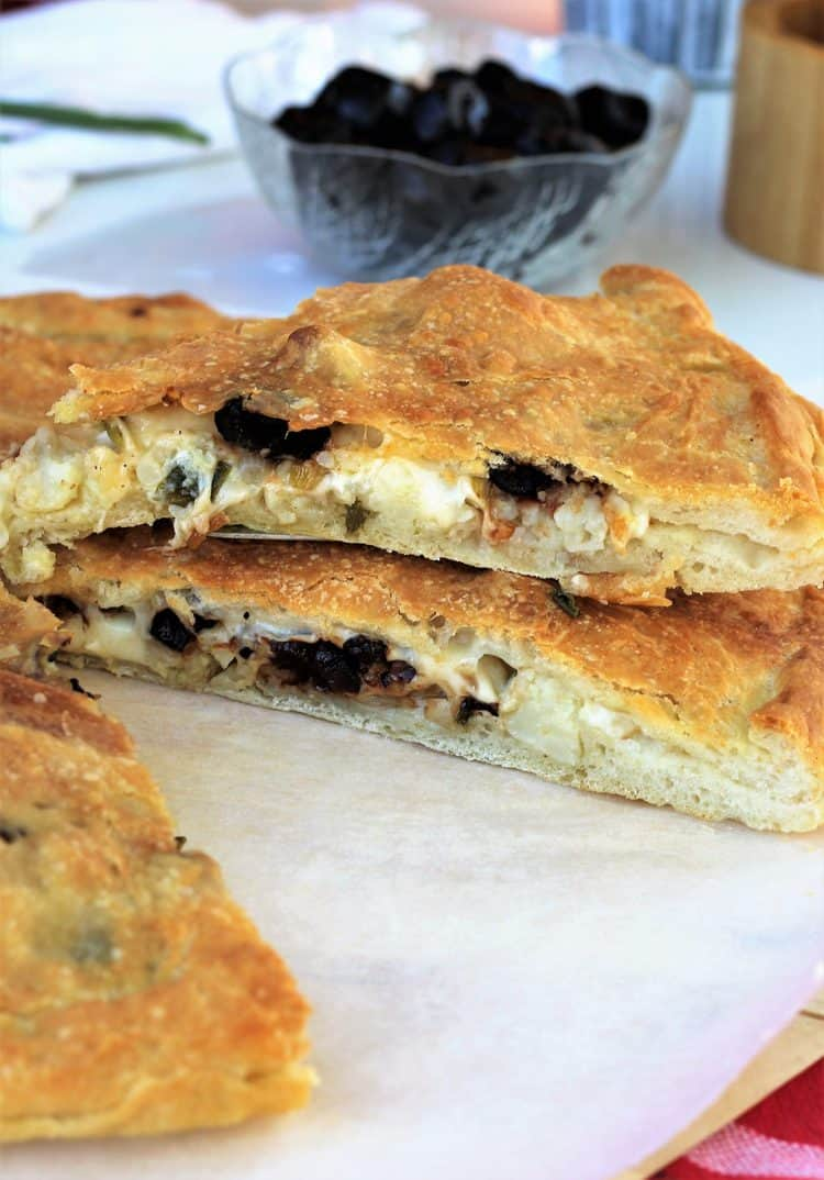 wedges of cauliflower and black olive filled pizza stacked