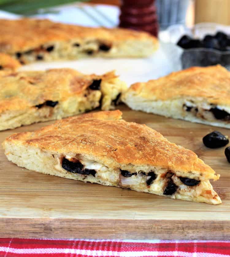 wedge of double crusted pizza filled with cauliflower and black olives on wood board