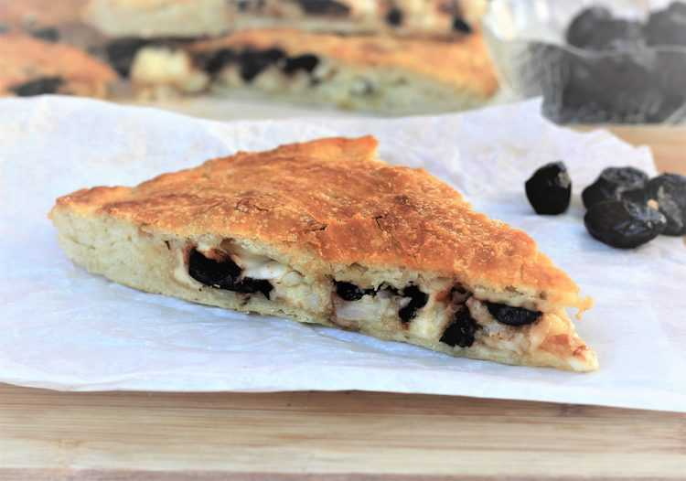 wedge of scacciata with cauliflower and black olives on parchment paper covered wood board