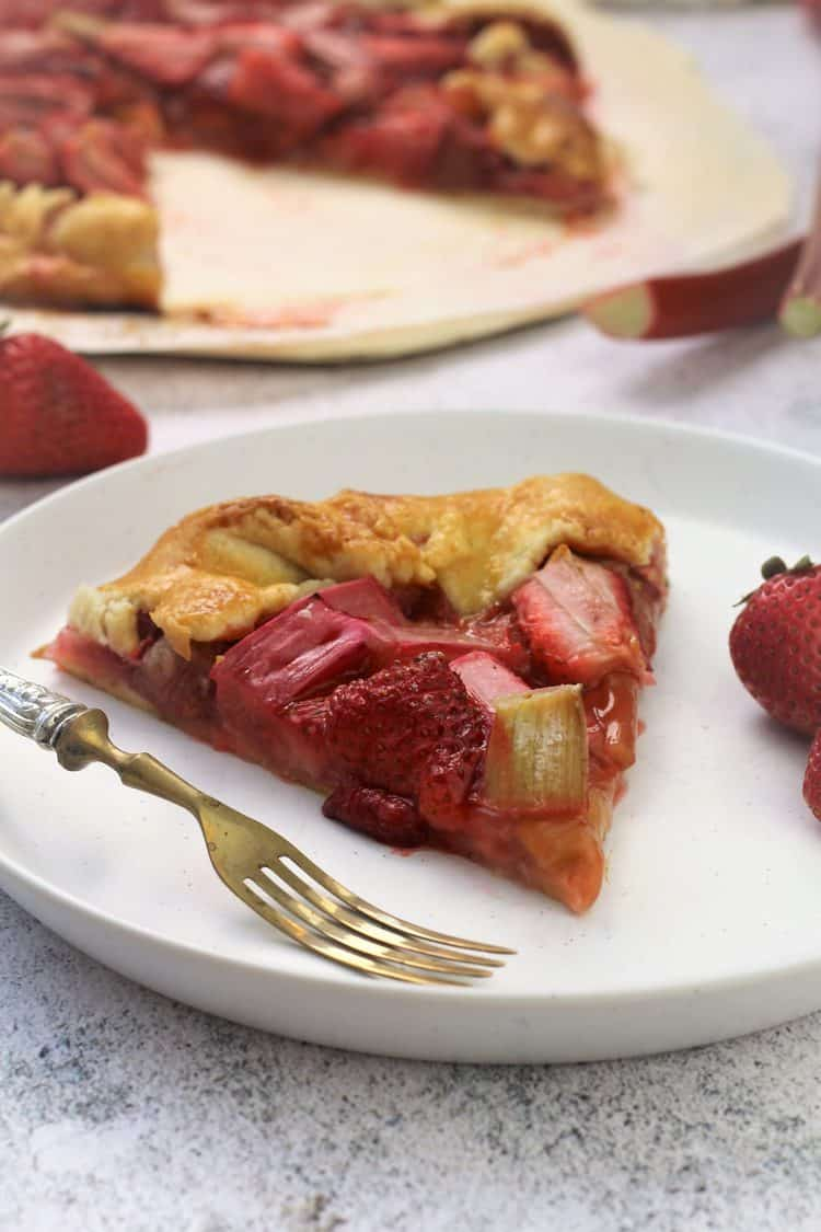 wedge of rhubarb strawberry crostata on white plate with strawberries and fork