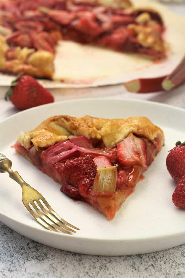 wedge of rhubarb strawberry crostata on white plate with fork and strawberries