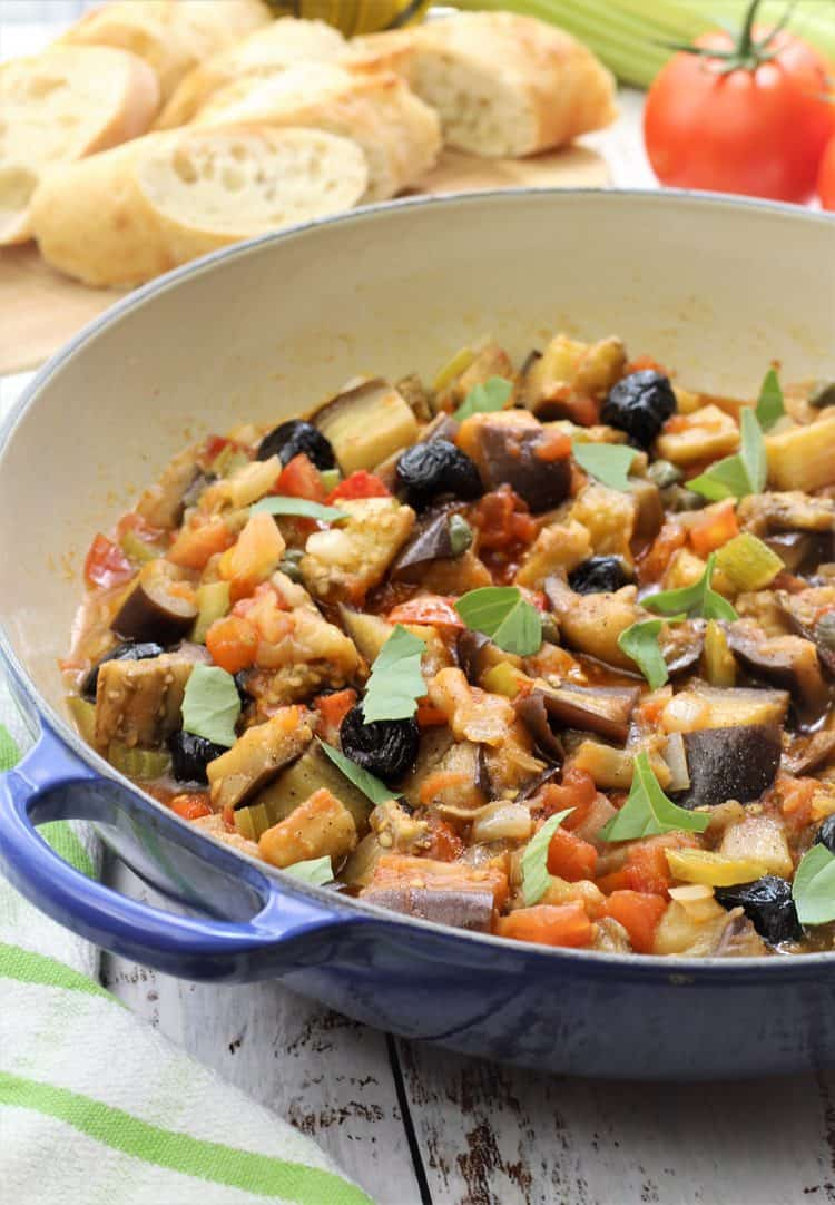 blue skillet filled with eggplant caponata with crostini and tomato in background
