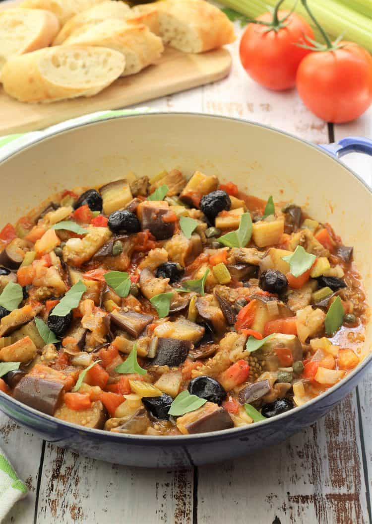 large blue skillet filled with eggplant caponata topped with basil leaves